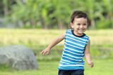 little boy running on the green nature