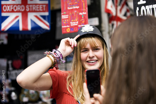A teenage girl trying on a policeman's helmet in a souvenir shop
