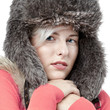 Beautiful winter lady with pelt cap feeling cold
