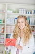 freundliche apothekerin zeigt gutschein