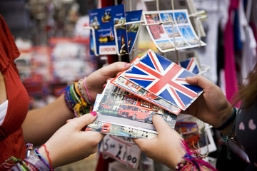 Two teenage girls choosing postcards in a souvenir shop