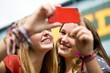 Two teenage girls taking a photograph in Camden, London