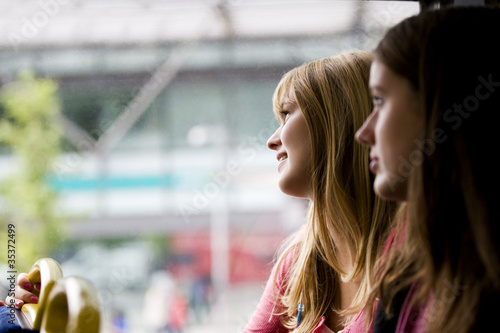 A teenage girl looking out of the window of a bus