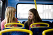 Two teenage girls sitting on a bus, having a conversation