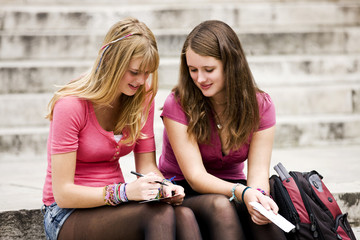 Two teenage girls sitting on steps, writing postcards