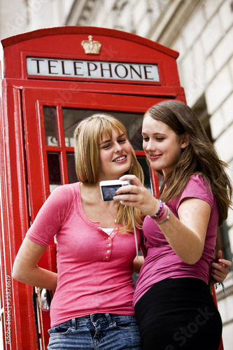 Two teenage girls taking photographs in front of a telephone box
