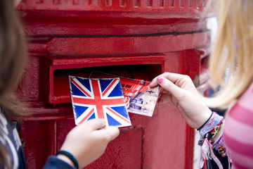 Two teenage girls putting postcards into a red letterbox