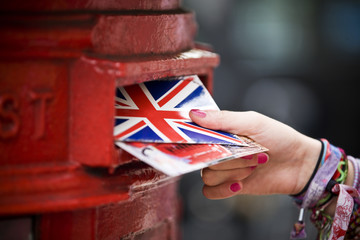 A teenage girl putting postcards into a red letterbox