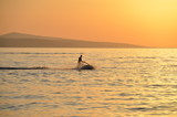 The silhouette of the man on the water scooter during sunset
