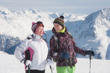 Alpine skiers ( mother and daughter) mountains in the background