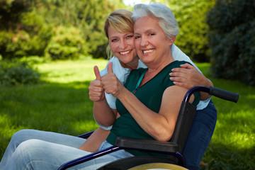Seniorin und Pflegerin heben Daumen hoch