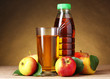 Apple juice and apples on wooden table on brown background