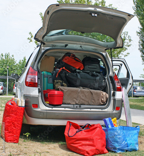 family car with suitcases and bags to return from vacation