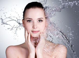 Splashes of water on the face of beautiful sexy woman