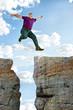 Mann springt von Fels zu Fels