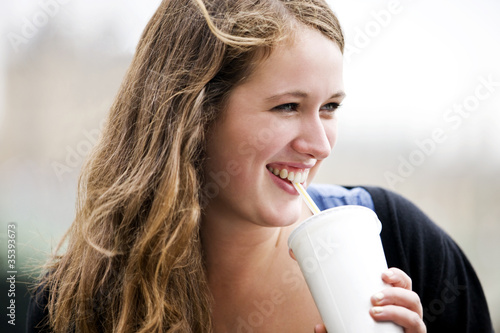 Portrait of a teenage girl drinking through a straw, smiling