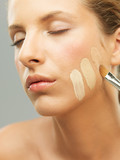 woman trying shades of foundation on jaw poster