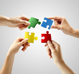 Fototapety Hands and puzzle on gray background. Teamwork solving a puzzle