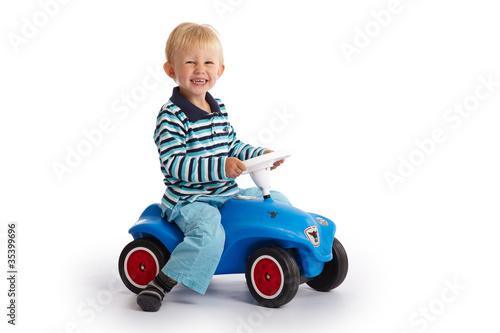 Leinwanddruck Bild Kleinkind fährt mit dem Bobby Car
