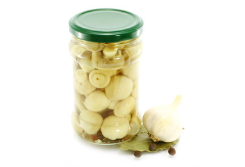 Glass jar of preserved mushrooms with garlic