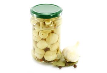 Glass jar of preserved mushrooms with garlic