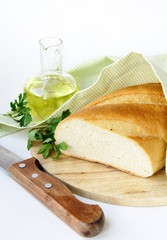 fresh white loaf of bread with a knife , olive oil