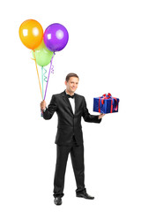 Butler with bow tie holding balloons and a gift