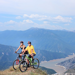 Young female and male posing with a mountain bikes