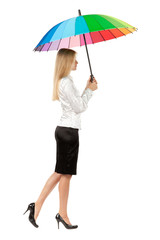 Full length, side view of young business woman under umbrella