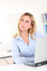 Blond woman at work with thoughtful look