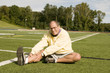middle age senior man exercising on sports field