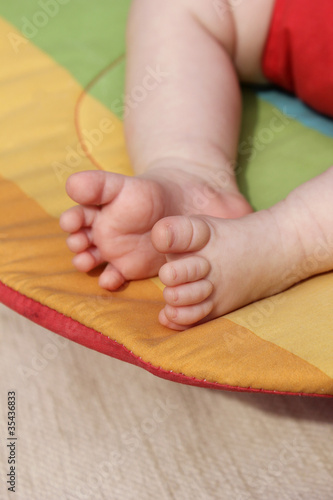 Newborn baby feet on a rainbow background