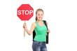 A young woman holding a traffic sign stop