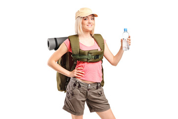 A woman hiker with backpack holding a bottle of water