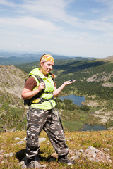 girl -  tourist in mountains is guided on a compass