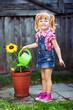 Cute girl watering a sunflower