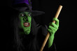 Witch flying on her broomstick. Black background.