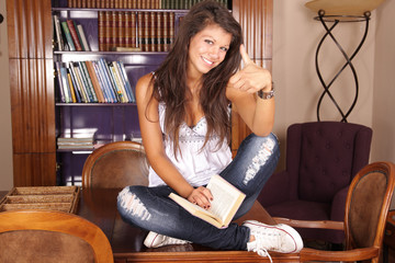 Thumbs up - teenager with a book sitting on a desk