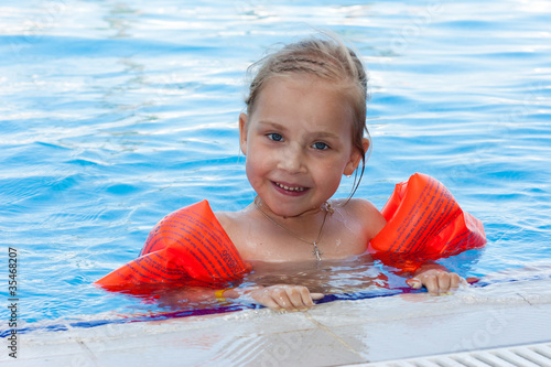 Adorable girl in armbands in swimming pool