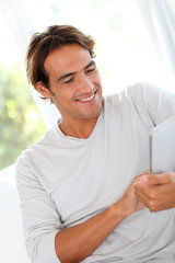 Smiling man using touchpad at home