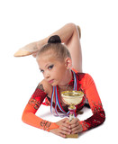 young gymnast lay with medal and prize cup