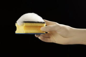mano con guante de latex con esponja con jabón en fondo negro