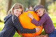 two girls proud of their big pumpkin