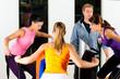 Frauen und Trainer in Fitness Studio vor Trainingsmaschine