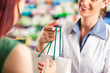Leinwanddruck Bild - Female pharmacist in her pharmacy with a client