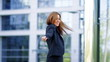 Happy business woman spins around outside office building