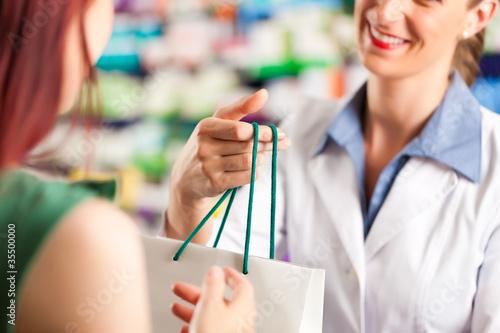 Leinwanddruck Bild Female pharmacist in her pharmacy with a client