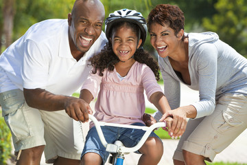African American Family WIth Girl Riding Bike & Happy Parents