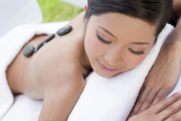 Woman Relaxing At Health Spa Having Hot Stone Treatment Massage
