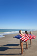 Three Young Women Wrapped in American Flags on a Beach